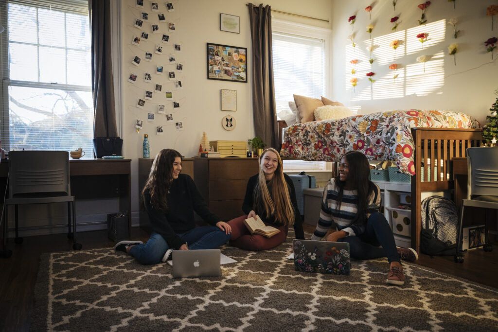 Three students sit on the floor with laptops in a residence hall room.