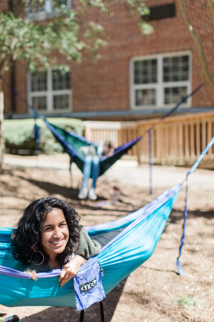 A student smiles at the camera from a hammock set up in front of the first year residence halls on Agnes Scot'ts campus.