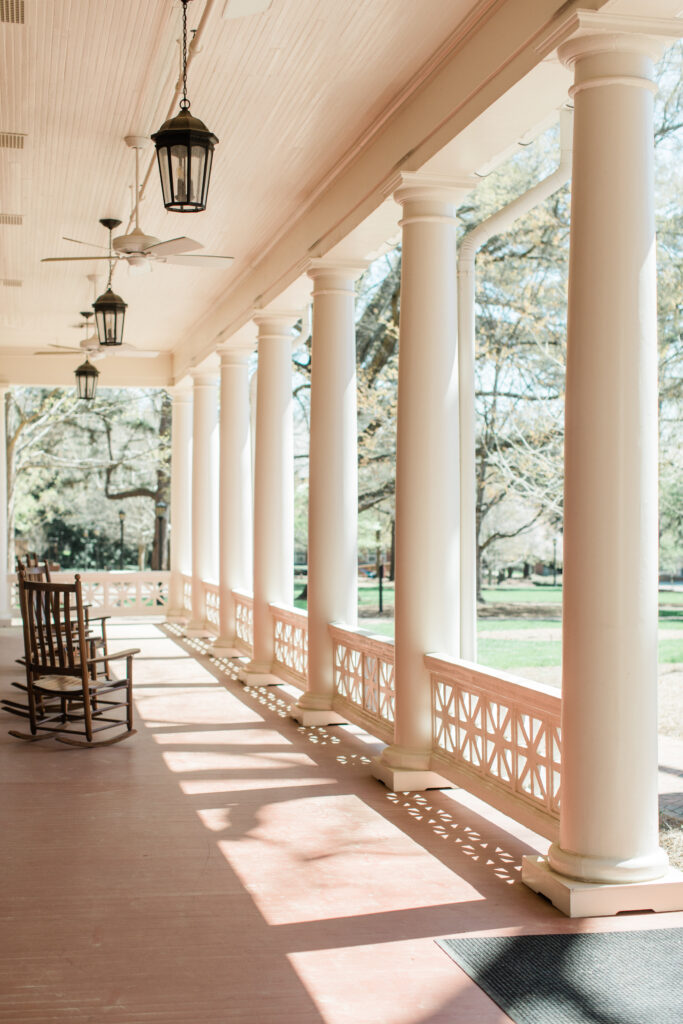 Exterior photo of a long front porch to Rebekah Hall, with several rocking chairs in view.