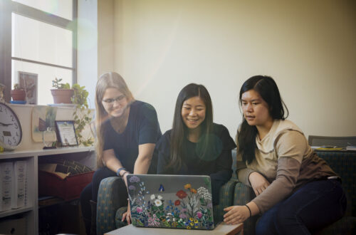 Three students gather around a computer.