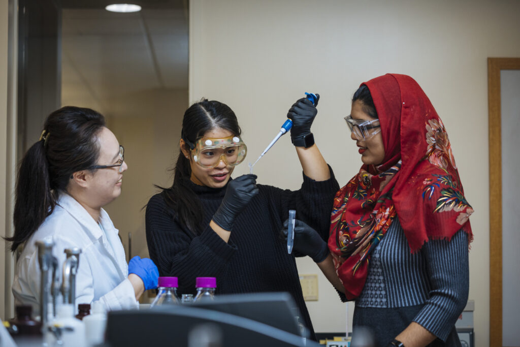 Image of two students and a professor in a lab