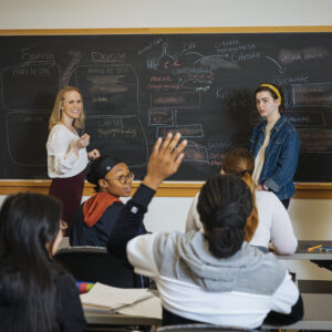 Students and Professor at a chalkboard while other students raise hands to answer a question.